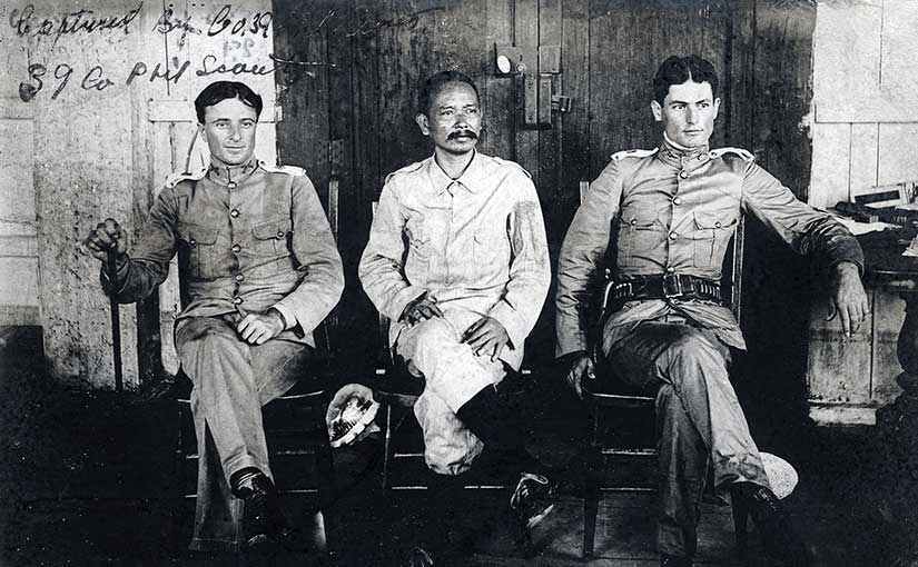 General Vicente Lukbán, center, who led the revolution on the islands of Samar and Leyte. He is seated with 1st Lt. Alphonse Strebler, 39th Philippine Scouts, and 2nd Lt. Ray Hoover, 35th Philippine Scouts. Image in the public domain from the Library of Congress, scanned by Scott Slaten.