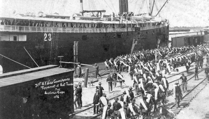 A black and white photo taken in 1898 of soldiers loading a ship at Port Tampa during the Spanish American War.