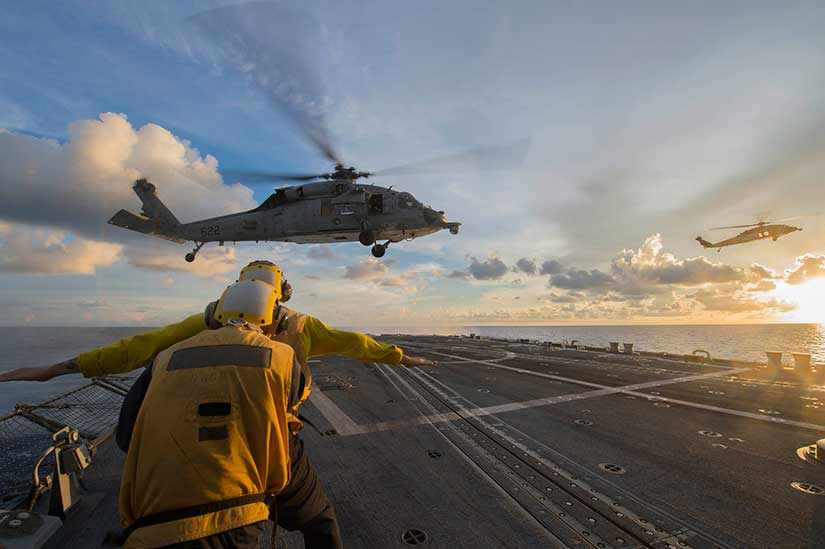 "Sailors signal to an MH-60S Sea Hawk helicopter attached to the ""Golden Falcons"" of Helicopter Sea Combat Squadron (HSC) 12 as it hovers over the flight deck of the Arleigh-Burke-class guided-missile destroyer USS McCampbel in the South China Sea. Photo by the US Navy."